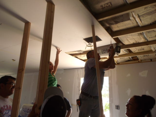 BNHR members work together to install the ceiling in the Laura Aguilar Human Rights Community Center in the Montana Vista area of East El Paso. The community worked for months to build the center form the ground up.